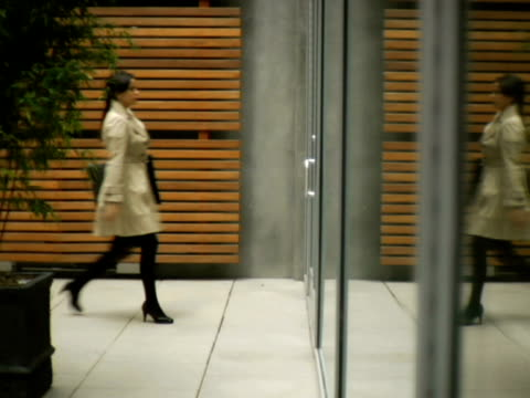 ws, woman walking through glass door, new york city, new york, usa - side view stock videos & royalty-free footage