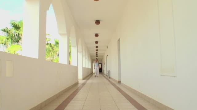 長い廊下を歩いて女性のアラビア風の構造 - 建築上の特徴 アーチ点の映像素材/bロール