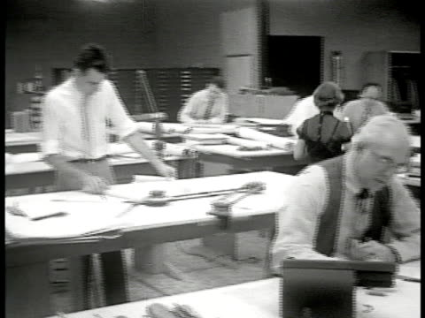 vídeos y material grabado en eventos de stock de woman walking through office delivering rolled paper passing architects draftsmen working designing at large tables ms men working - arquitecta