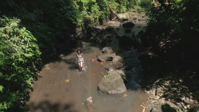 ts: frau zu fuß durch fluss - tropischer regenwald stock-videos und b-roll-filmmaterial