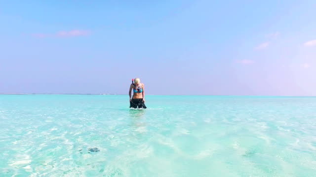woman walking through shallow water on maldives - water sports equipment stock videos and b-roll footage