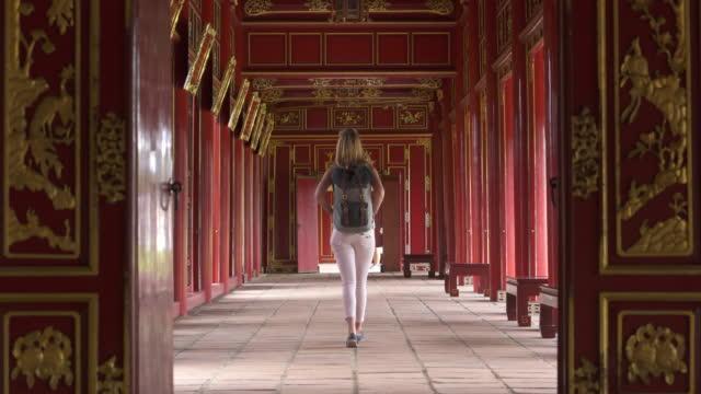 vídeos y material grabado en eventos de stock de mujer caminando por el pasillo del templo - encontrar