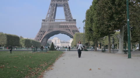 stockvideo's en b-roll-footage met ws woman walking through the champs de mars with eiffel tower in the background / paris, france - 2010