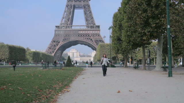 ws woman walking through the champs de mars with eiffel tower in the background / paris, france - 2010 stock videos & royalty-free footage