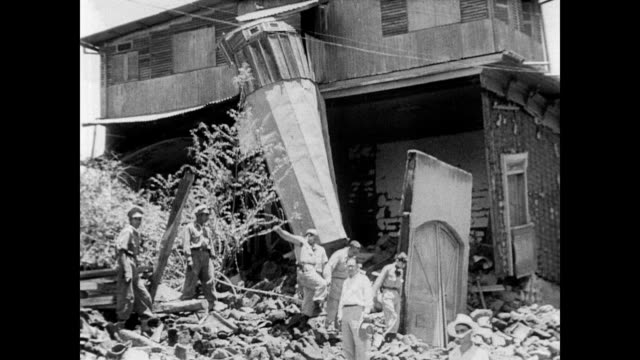 vídeos y material grabado en eventos de stock de / woman walking through the rubble in jucuapa el salvador after a devastating earthquake / men walk around destroyed church / military troops mill... - 1951