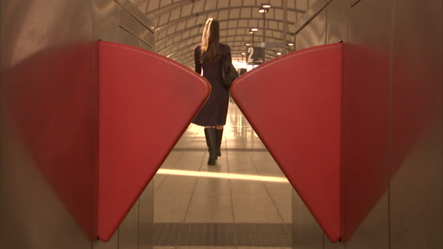 CU, Woman walking through ticket barriers at Olympic Park railway station, rear view, Sydney, Australia