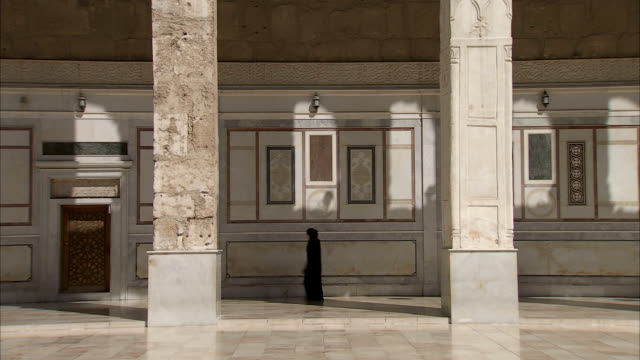woman walking through umayyad mosque (great mosque of damascus), damascus, syria - grand mosque stock videos and b-roll footage