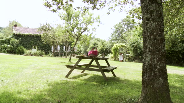 vídeos de stock e filmes b-roll de ms woman walking to and sitting down at picnic table in front of house in garden / saint junien, central france, france - mesa de piquenique