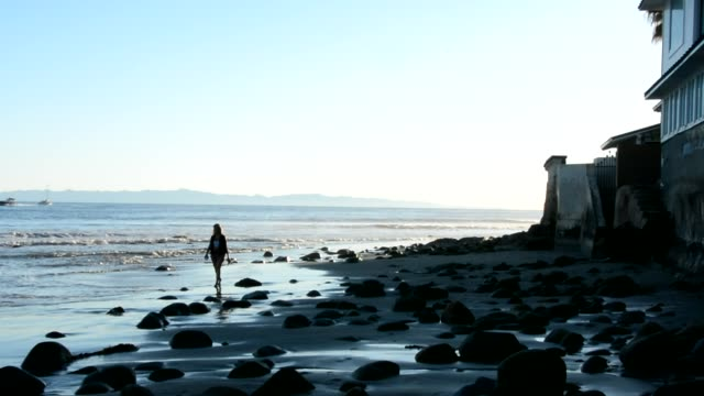 woman walking to camera at the beach. large smooth black rocks in the shade. sunny afternoon montecito santa barbara beach. - santa barbara california stock videos & royalty-free footage