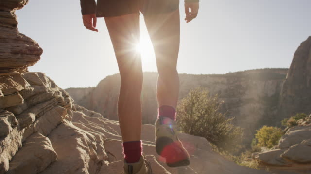 woman walking to edge of cliff at sunrise - canyon stock videos and b-roll footage