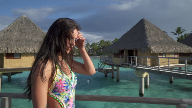 a woman walking to her overwater bungalow, lifestyle at a tropical island resort. - french polynesia stock videos & royalty-free footage