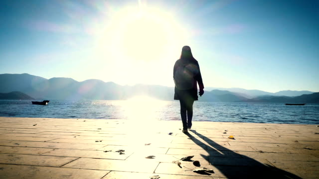woman walking to lake on wooden pier