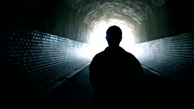 woman walking to light in dark tunnel - tunnel stock videos & royalty-free footage
