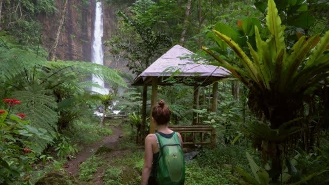 woman walking to powerful waterfall on java - java stock videos & royalty-free footage