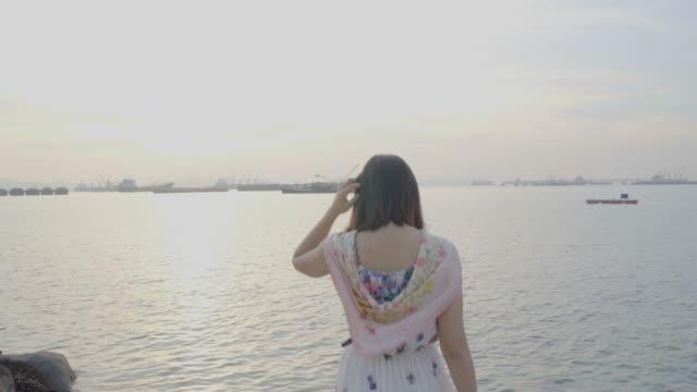 stockvideo's en b-roll-footage met vrouw lopen naar de zee in de ochtend. - menselijke rug