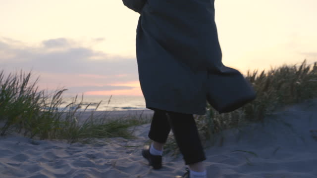 woman walking to the beach at sunset - grass family stock videos & royalty-free footage