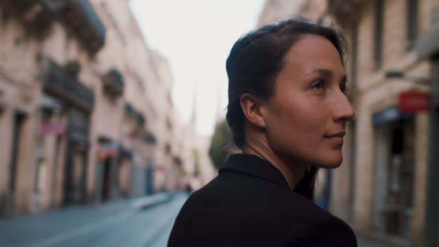 woman walking toward cathedral in bordeaux - brown hair stock videos & royalty-free footage