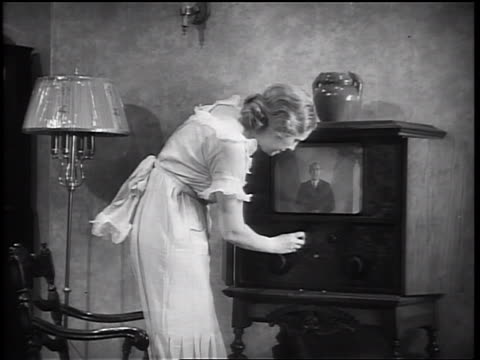 B/W 1933 PAN woman walking toward + sitting in front of TV set / zoom in man on TV w// suit talking