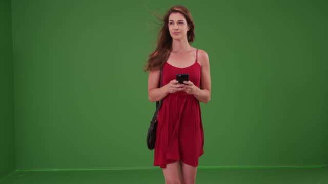 woman walking toward the camera in a red dress on smart phone on green screen - dress stock videos & royalty-free footage