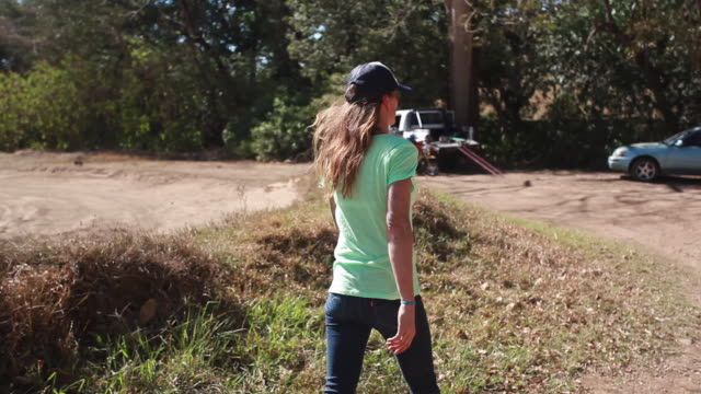 vidéos et rushes de a woman walking towards a young boy on a dirt bike and a pickup truck on a sunny summer day - kelly mason videos