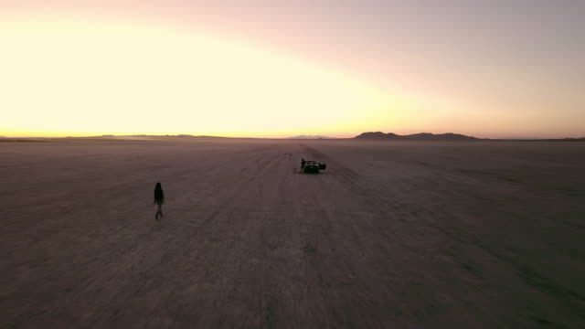 woman walking towards man and car in mojave desert - lake bed stock videos & royalty-free footage