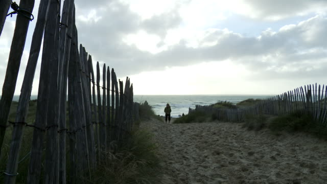 MS Woman walking up sandy path on beach in wind at evening / Soulac-sur-Mer, Aquitaine, France