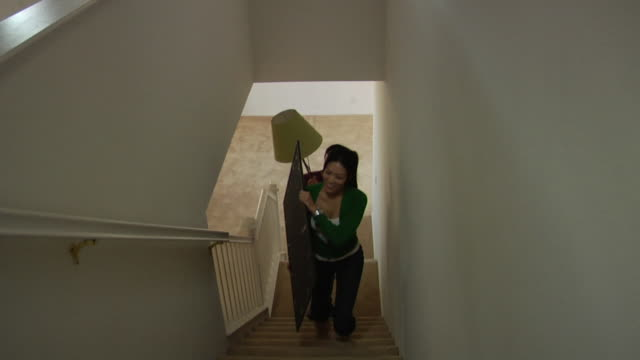 vídeos de stock e filmes b-roll de ha ws woman walking up stairs carrying mirror followed by man carrying floor lamp in new house / los angeles, california, usa - homens de idade mediana