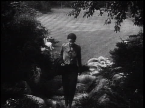 b/w 1931 woman walking up stairs in park toward camera / turning + looking behind her - 1931 stock videos & royalty-free footage