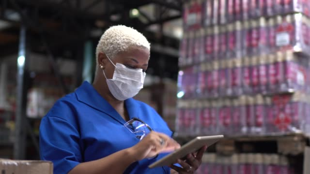 vídeos de stock e filmes b-roll de woman walking using digital tablet wearing face mask - working at warehouse / industry - employee