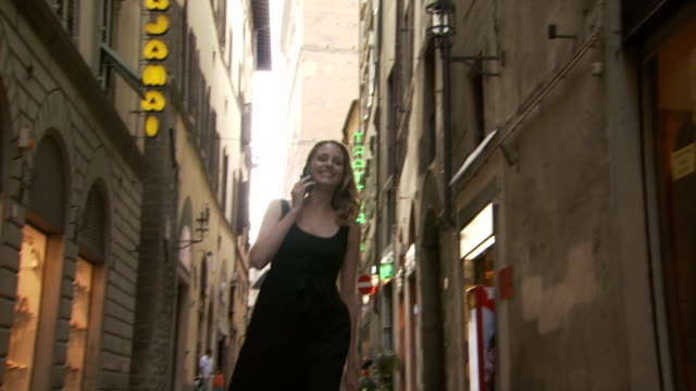 a woman walking while on her cellular phone - see other clips from this shoot 1150 stock videos and b-roll footage