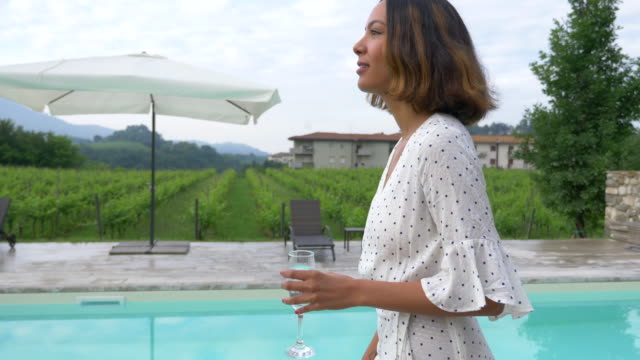 stockvideo's en b-roll-footage met a woman walking with a glass of white wine at a pool traveling at a luxury resort in italy, europe. - slow motion - elegantie