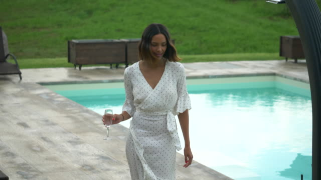a woman walking with a glass of white wine at a pool traveling at a luxury resort in italy, europe. - slow motion - goodsportvideo stock videos and b-roll footage