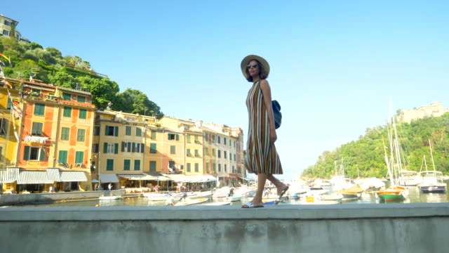 a woman walking with a hat and backpack purse traveling in portofino, italy, a luxury resort town in europe. - slow motion - sandal stock videos and b-roll footage