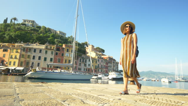 A woman walking with a hat and backpack purse traveling in Portofino, Italy, a luxury resort town in Europe. - Slow Motion