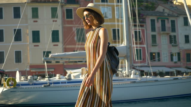 a woman walking with a hat and backpack purse traveling in portofino, italy, a luxury resort town in europe. - slow motion - italian culture stock-videos und b-roll-filmmaterial