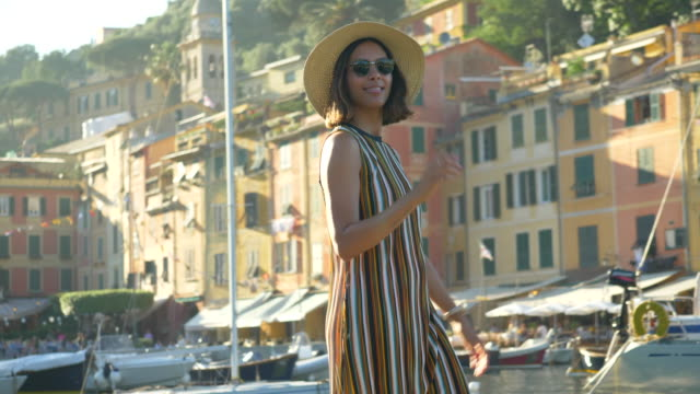 vídeos y material grabado en eventos de stock de a woman walking with a hat and backpack purse traveling in portofino, italy, a luxury resort town in europe. - slow motion - vestido