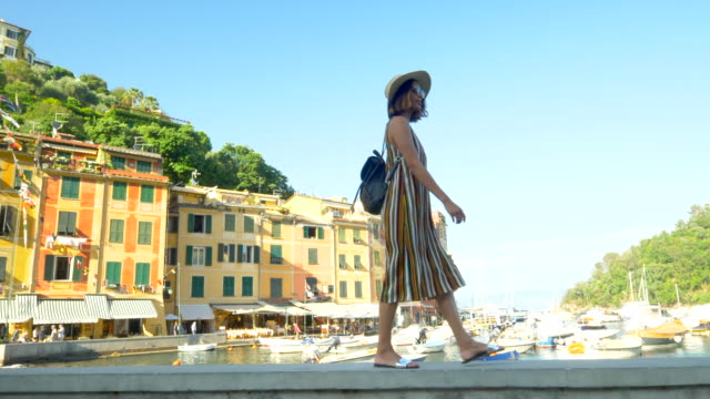 a woman walking with a hat and backpack purse traveling in portofino, italy, a luxury resort town in europe. - slow motion - italienische kultur stock-videos und b-roll-filmmaterial