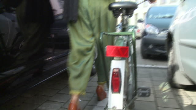 ms woman walking with bicycle through parking lot, gent, belgium - platform shoe stock videos and b-roll footage