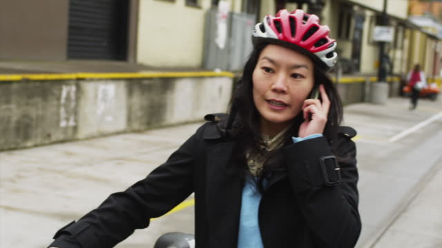 ms tu td woman walking with bicycle while using mobile phone / portland, oregon, usa - portland oregon bike stock videos & royalty-free footage