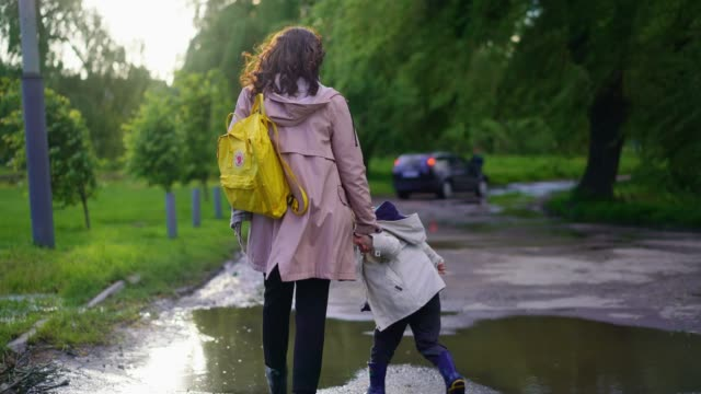 woman walking with boy  in park after the rain - primary age child stock videos & royalty-free footage