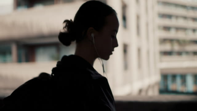 woman walking with headphones and smart phone in city - rucksack stock videos & royalty-free footage