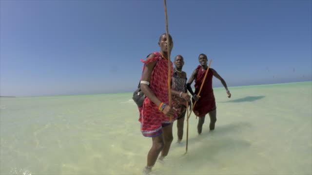 a woman walking with her kiteboarding kite near some native locals in zanzibar, tanzania. - minoranza video stock e b–roll
