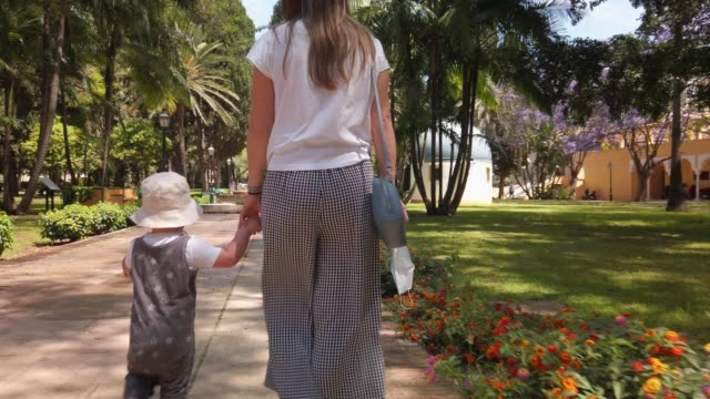 woman walking with her son - handbag stock videos & royalty-free footage