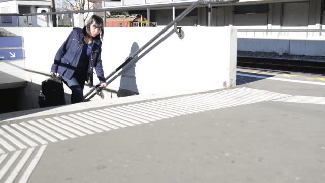 vídeos de stock, filmes e b-roll de woman walking with her wheelie suitcase - jaqueta jeans