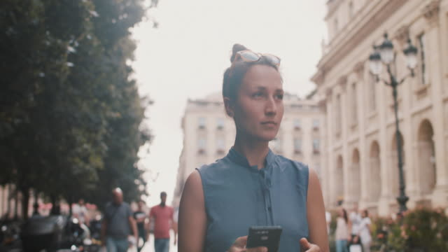 woman walking with phone in bordeaux in the summer - street stock videos & royalty-free footage