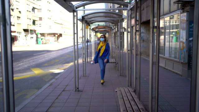 woman walking with protective mask on face - bus stop stock videos & royalty-free footage