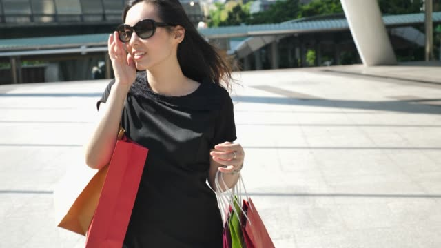 woman walking with shopping bag in city, woman lifestyle - shopping bag stock videos and b-roll footage