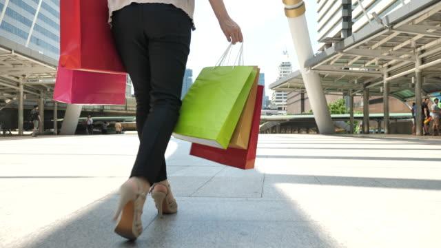 vídeos y material grabado en eventos de stock de mujer caminando con bolsa, ángulo bajo - encuadre de cuerpo entero
