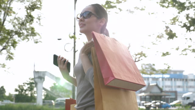 woman walking with shopping bag on sunlight - shopping bag stock videos and b-roll footage
