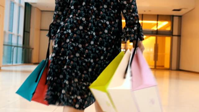 stockvideo's en b-roll-footage met vrouw lopen met boodschappentassen op winkelcentrum - cadeau